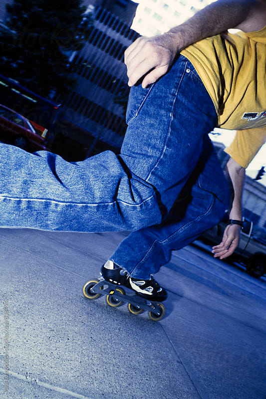 Low angle view of man rollerblading on urban sidewalk by Paul Edmondson for Stocksy United