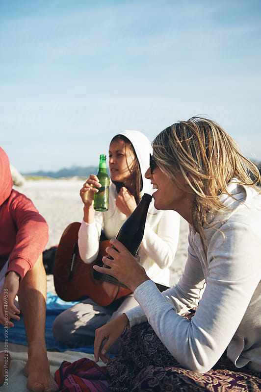 Beach drinking friends by Daxiao Productions for Stocksy United