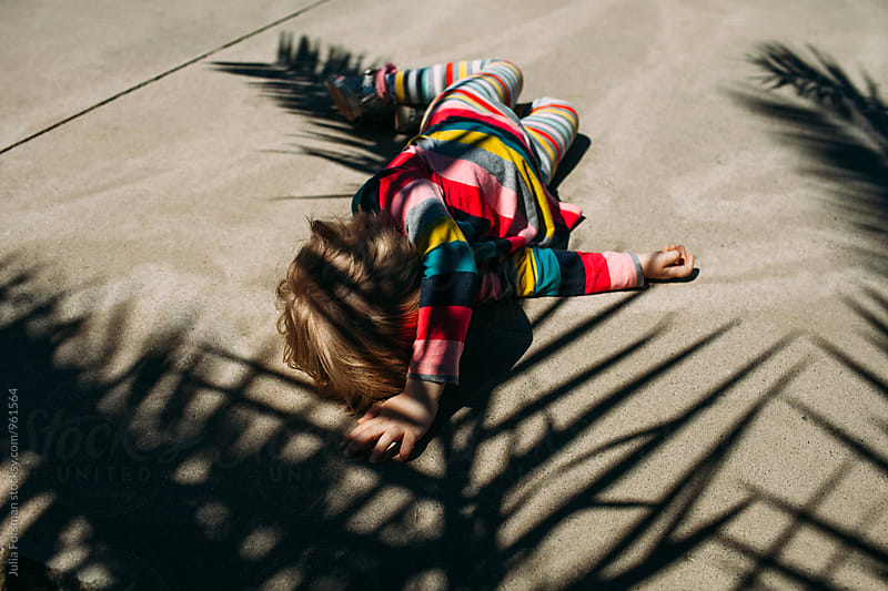 Little girl lies on the pavement in the shade of a palm tree. by Julia Forsman for Stocksy United