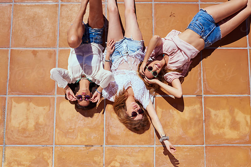 Three young friends having fun while lying on floor in sunlight by Guille Faingold for Stocksy United