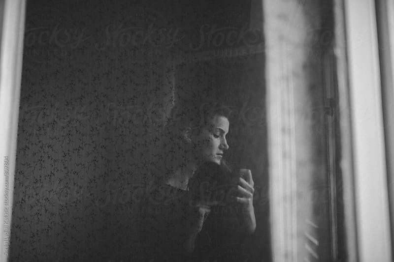 Self portrait in a reflective window in black  and white by Sanja (Lydia) Kulusic for Stocksy United