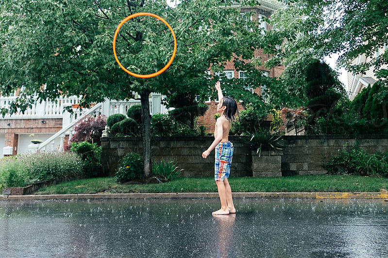 Young Boy Plays With Hula Hoop in Rain by kelli kim for Stocksy United