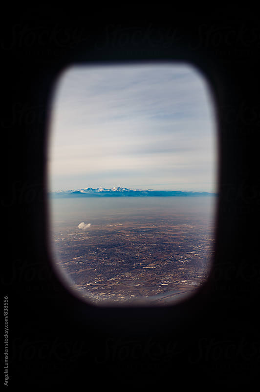 Goodbye to Denver and the Rocky Mountains through an airplane window by Angela Lumsden for Stocksy United