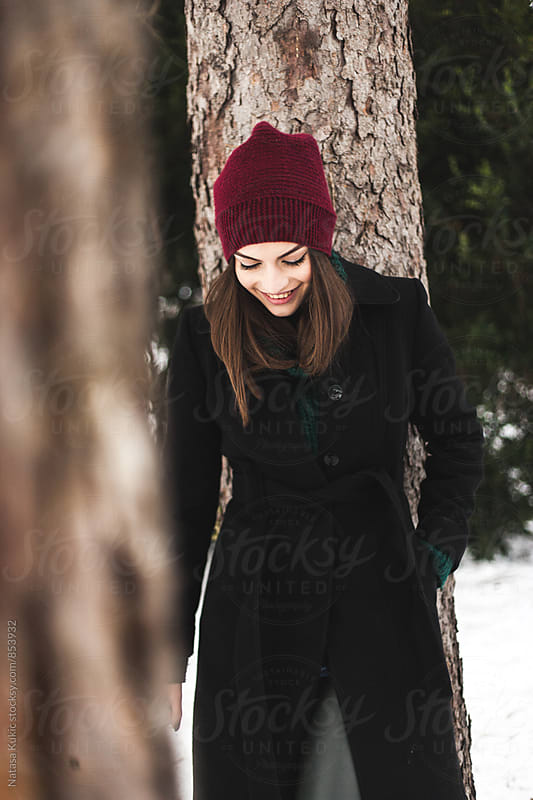 Winter portrait of a beautiful brunette leaning against the tree by Natasa Kukic for Stocksy United