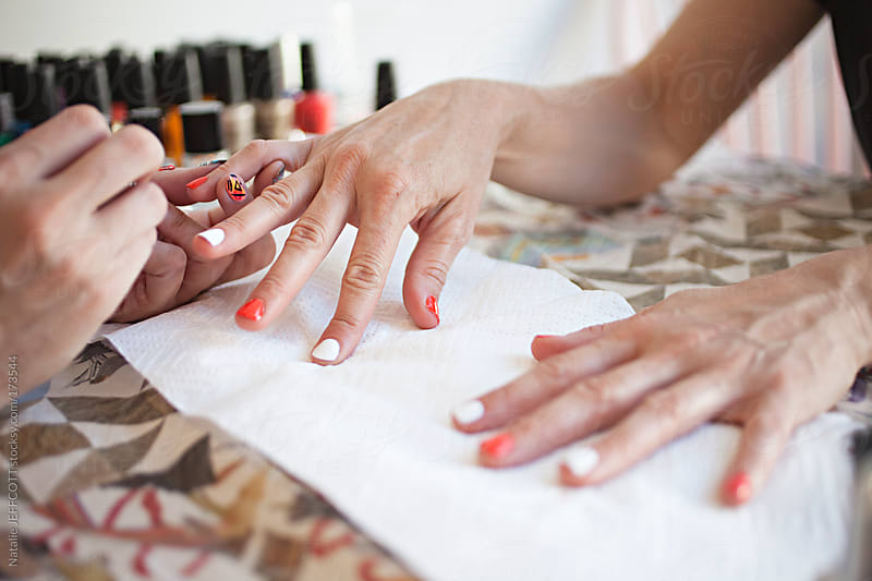 A lady's hands on colourful table receiving a manicure / nail art by Natalie JEFFCOTT for Stocksy United