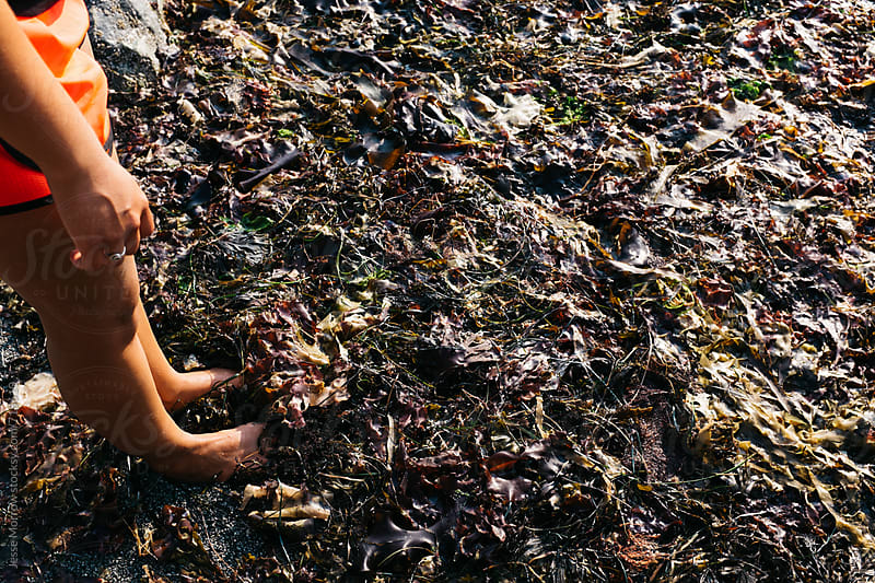 young female walking through seaweed on beach by Jesse Morrow for Stocksy United