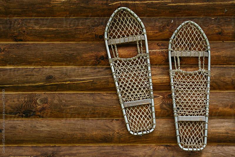 Pair of snow shoes on a log cabin wall by Gabriel (Gabi) Bucataru for Stocksy United