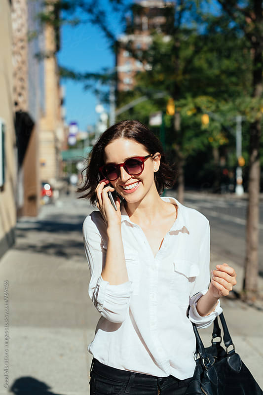 Smiling woman talking at the phone by Good Vibrations Images for Stocksy United