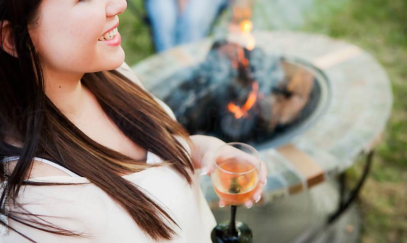 Party: Woman Having Wine By Fire by Sean Locke for Stocksy United