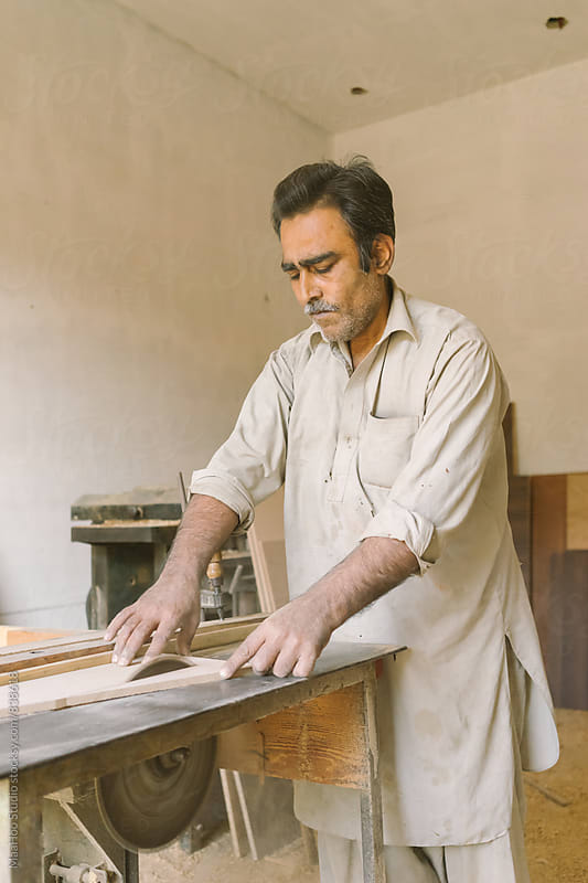 Carpenter working on machine by MaaHoo Studio for Stocksy United