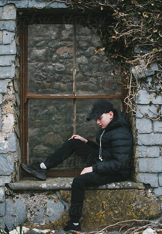 Teenage boy in sportswear sitting in front of the window of a derelict building. by Helen Rushbrook for Stocksy United