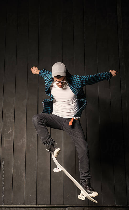 Young skater in urban outfit jumping and doing tricks. by Audrey Shtecinjo for Stocksy United