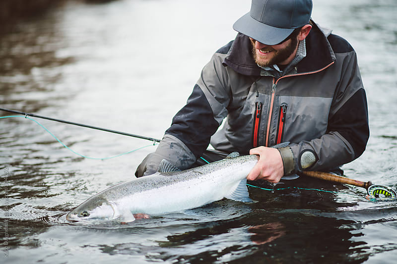 Happy fly fisherman with a winter steelhead he caught.  by Kate Daigneault for Stocksy United