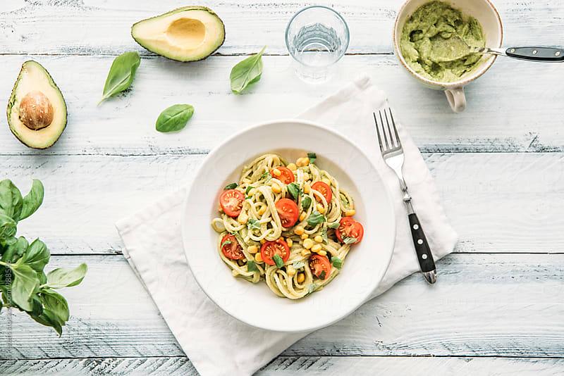 Food: Spaghetti with vegan avocado pesto with garlic, basil, cherry tomato, lemon and corn by Ina Peters for Stocksy United