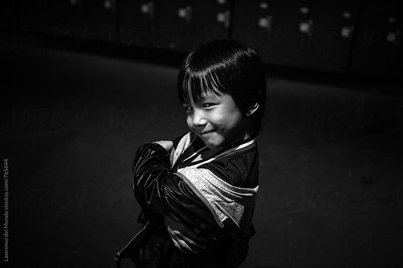 Black and white portrait of a young little kid smiling mischievously at the camera by Lawrence del Mundo for Stocksy United