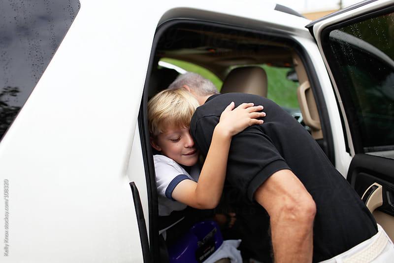 boy hugs grandfather goodbye by Kelly Knox for Stocksy United