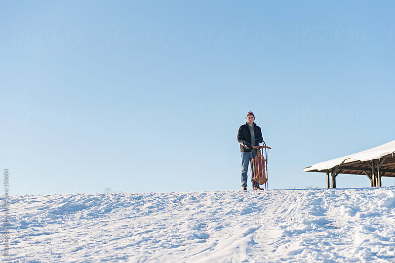 Man with runner sled on sledding hill by Brian McEntire for Stocksy United