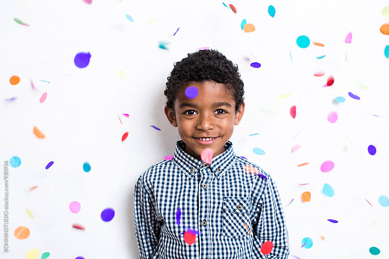 Portrait of a little boy enjoying as confetti falls from above. by BONNINSTUDIO for Stocksy United