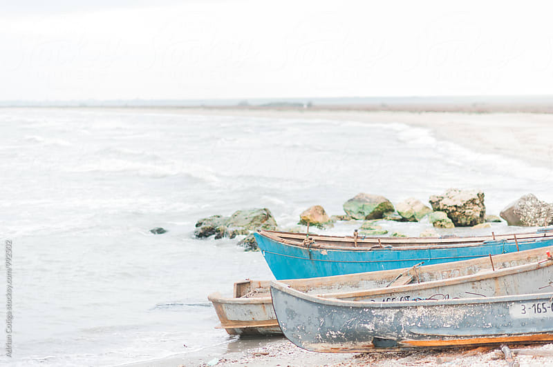 Old  boats moored on the beach by Adrian Cotiga for Stocksy United