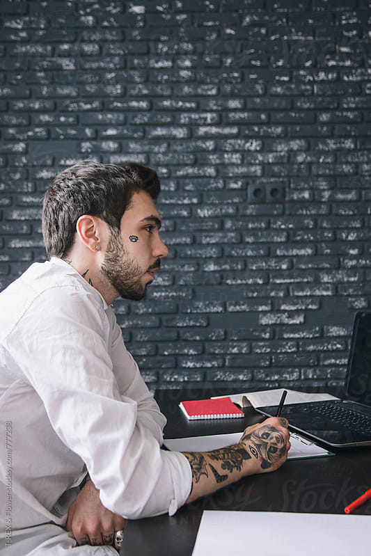 Young businessman sitting at desk by Danil Nevsky for Stocksy United