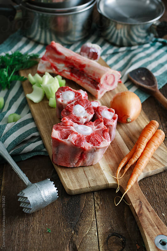 Beef bones and vegetables on a cutting board. by Darren Muir for Stocksy United