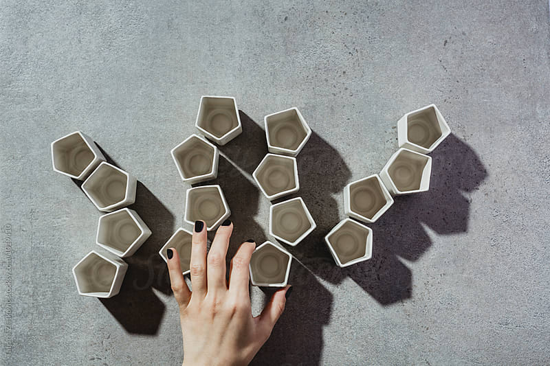 Hand is making shapes with ceramic cups by Tatjana Ristanic for Stocksy United