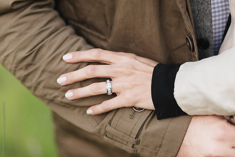 A diamond engagement ring on a female hand holding onto her partner by Ania Boniecka for Stocksy United