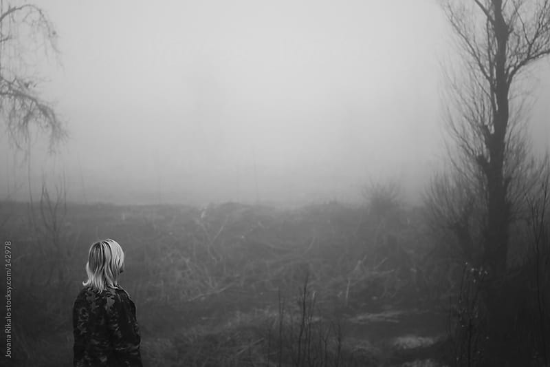 A young girl walking in a field with fog by Jovana Rikalo for Stocksy United