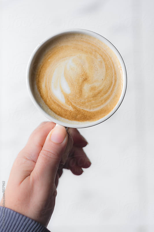 flat white coffee in my hand by Gillian Vann for Stocksy United