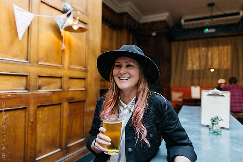 Woman drinking beer in a pub by Melanie Riccardi for Stocksy United