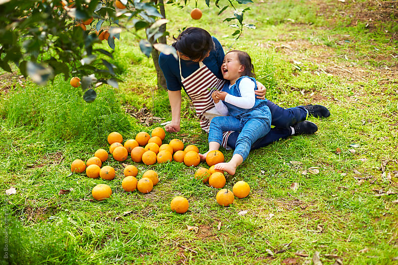 little asian girl having fun in the orange farm with her mother by cuiyan Liu for Stocksy United