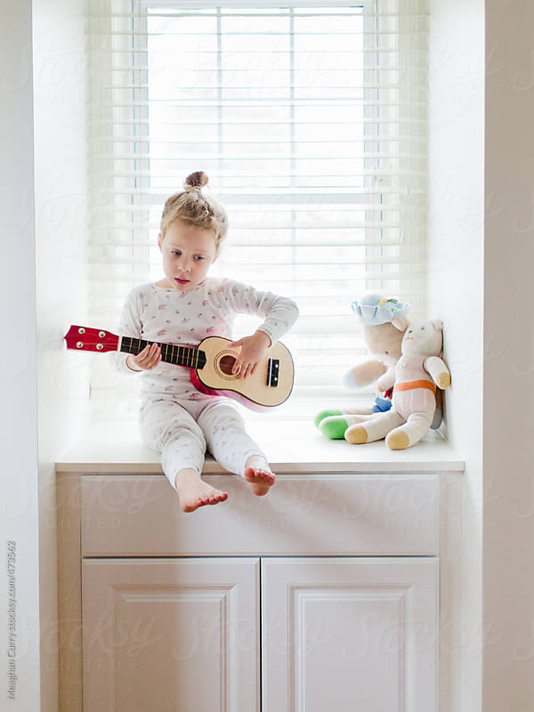 little girl playing a toy guitar in a window seat by Meaghan Curry for Stocksy United