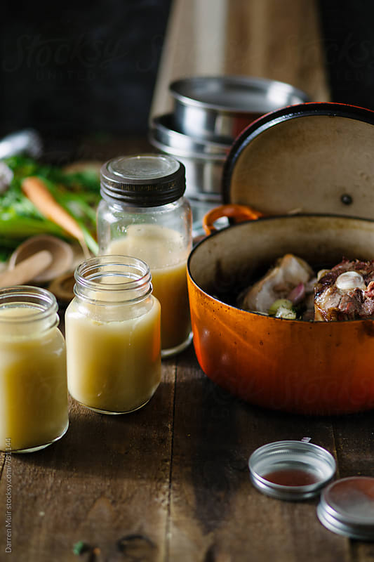 Bone broth in jars on a wooden surface next to a dutch oven. by Darren Muir for Stocksy United
