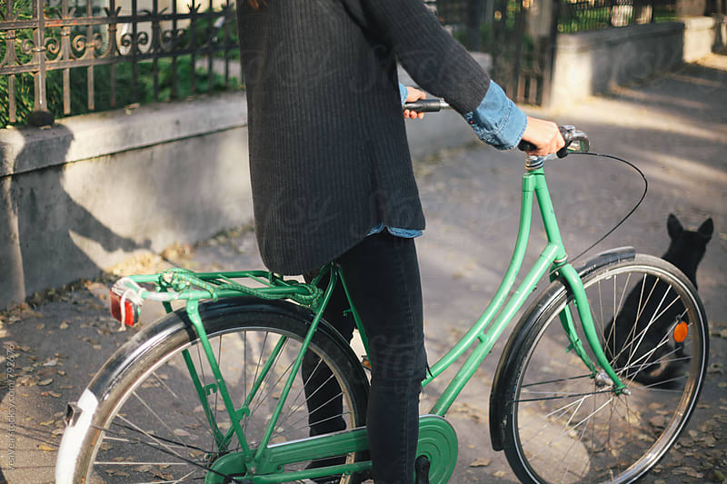Stylish woman with a green bicycle in the street. Just body. by Marija Mandic for Stocksy United