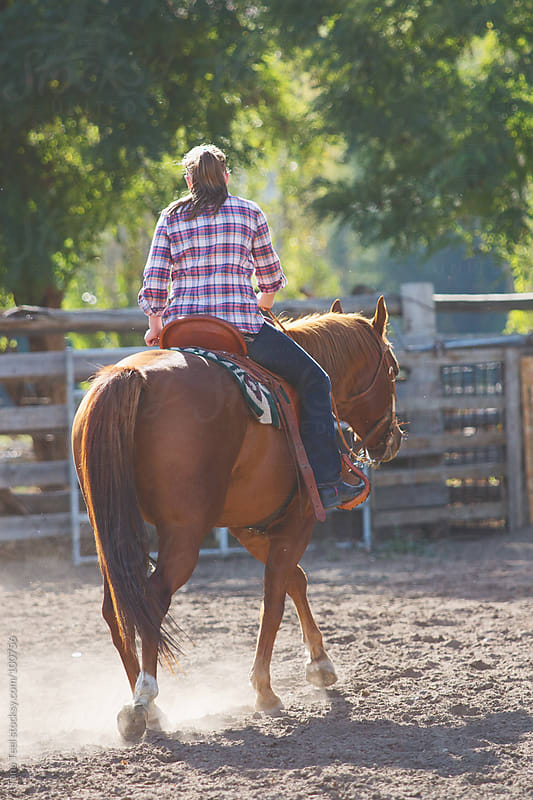 A rider riding her horse in an arena by Tana Teel for Stocksy United