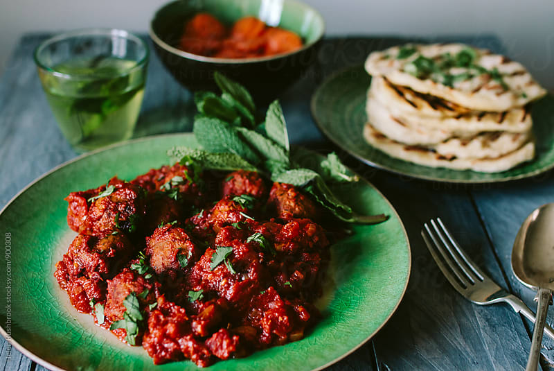 Lamb meatballs in a spiced tomato sauce with Moroccan side dishes. by Helen Rushbrook for Stocksy United