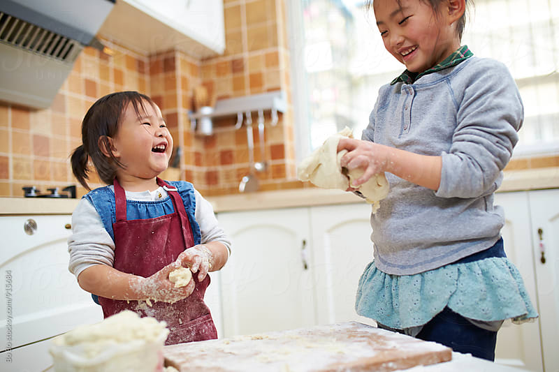 two little asian girls having fun in the kitchen by Bo Bo for Stocksy United