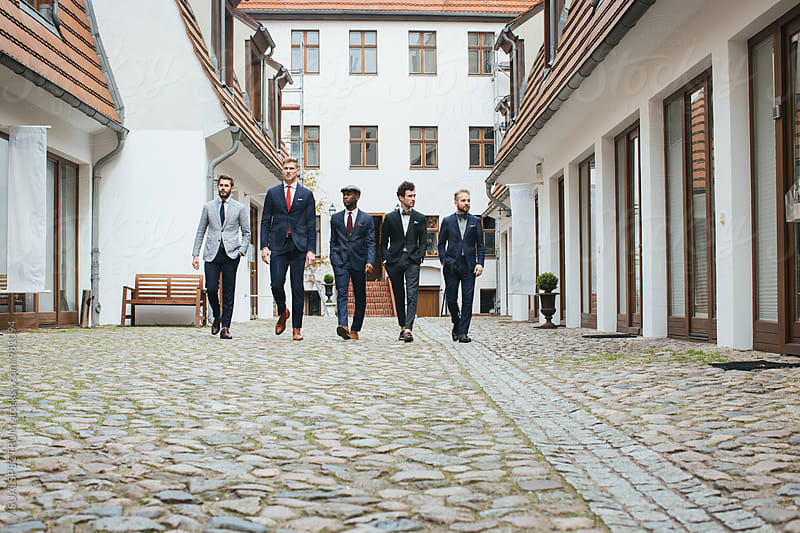 Five Stylish Young Men in Suits Walking Down in Courtyard by VISUALSPECTRUM for Stocksy United