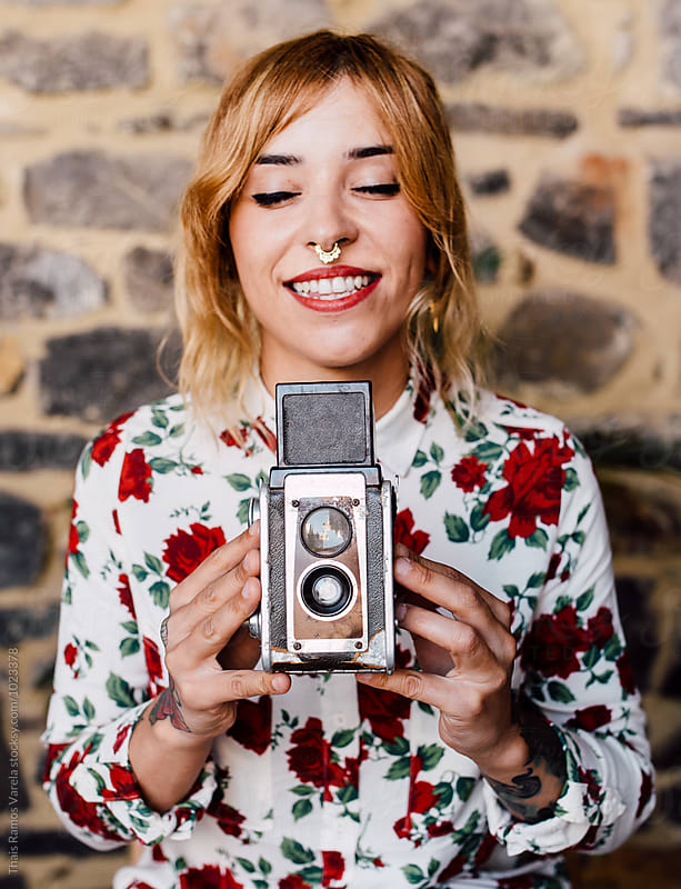 portrait of a woman with a camera by Thais Ramos Varela for Stocksy United