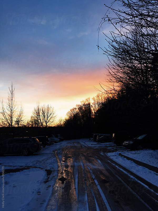 The sun sets over cars in a parking lot in winter.  by Holly Clark for Stocksy United