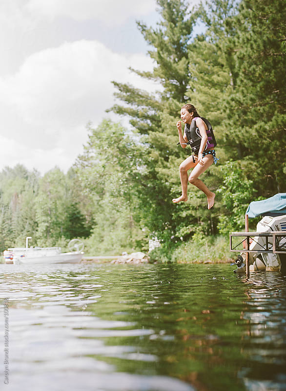 Girl jumping midair into a lake  by Carolyn Brandt for Stocksy United