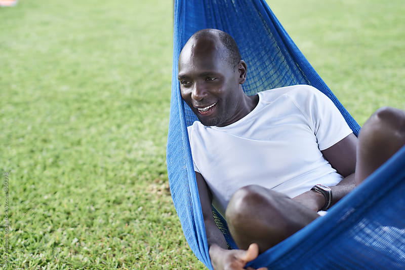 Black man relaxing on vacation in a garden by Per Swantesson for Stocksy United