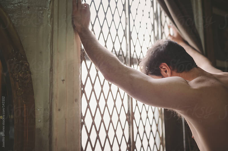 Shirtless Man Standing by Grated Window at Home by Joselito Briones for Stocksy United