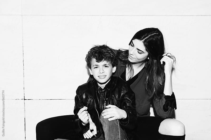 Boy looking at camera while his sister hugging him by Guille Faingold for Stocksy United