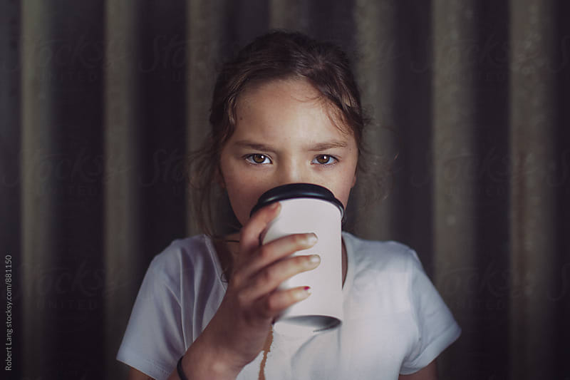 Young girl drinking takeaway coffee by Robert Lang for Stocksy United