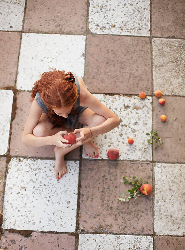 Young girl and fruit in a romantic mood by Miquel Llonch for Stocksy United