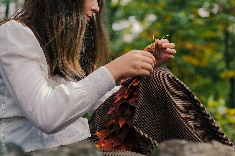 Girl Creating Maple Leaf Garland by Deirdre Malfatto for Stocksy United