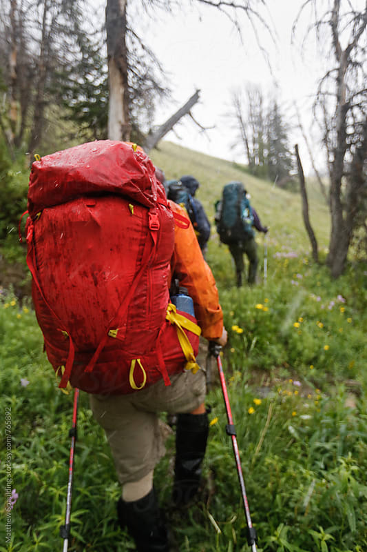 Hiker backpacking on trail in rain by Matthew Spaulding for Stocksy United