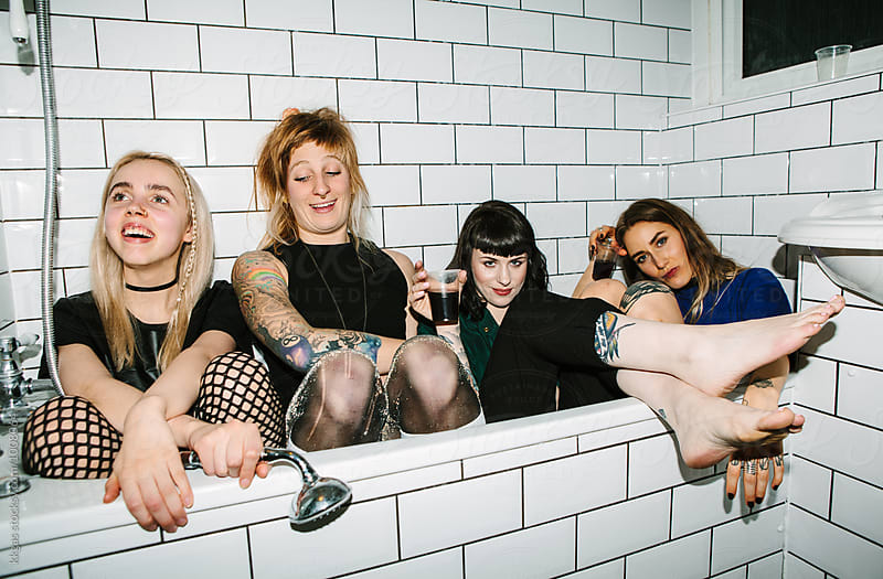 Four women inside a bath tub at a houseparty  by kkgas for Stocksy United