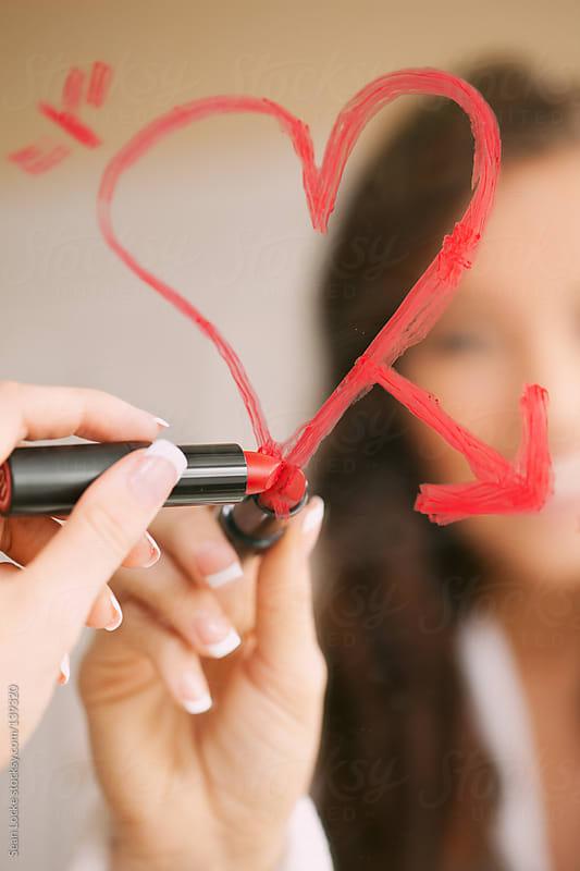 Valentine's: Woman Drawing Heart On Bathroom Mirror In Lipstick by Sean Locke for Stocksy United